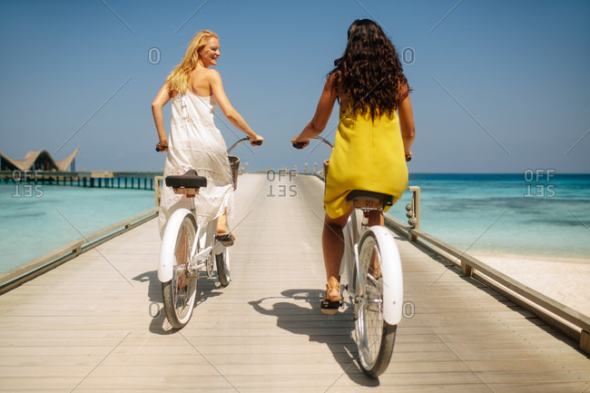 Friends on a holiday riding bicycles on a jetty. Rear view of two women having fun riding bicycles on a jetty at a luxury sea resort.