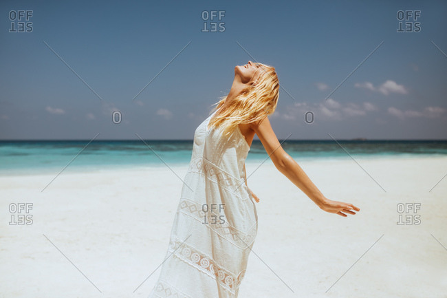 Side view of a woman standing on beach with closed eyes facing the sky. Woman on a holiday enjoying sea breeze and relaxing.