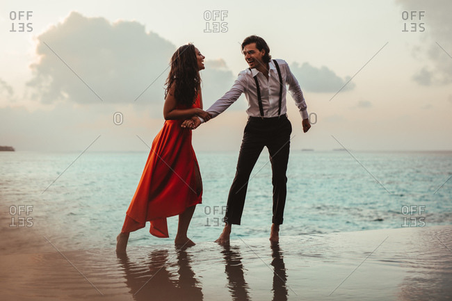 Formally dressed couple standing on the edge of an infinity pool at a sea resort. Happy couple spending romantic moments at a swimming pool.