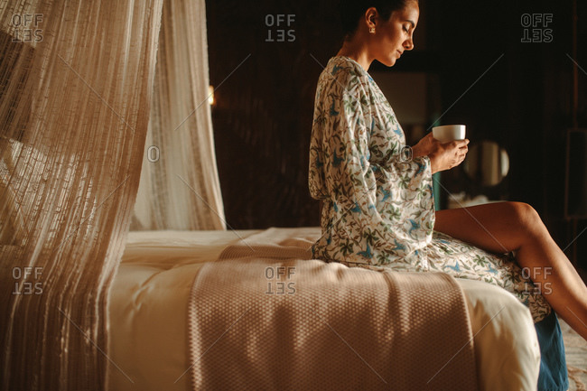 Woman sitting on bed holding a coffee cup. Side view of a woman sitting on bed drinking coffee.