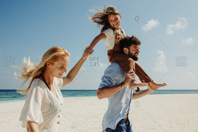 Man walking with wife on the beach carrying his daughter on shoulders. Couple with a kid on a beach holiday.