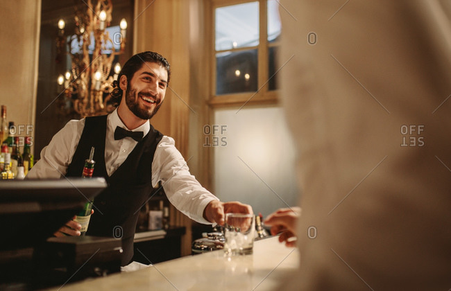 Barman serving a drink to man standing at bar counter during party. Bartender serving alcohol to guest at a nightclub.