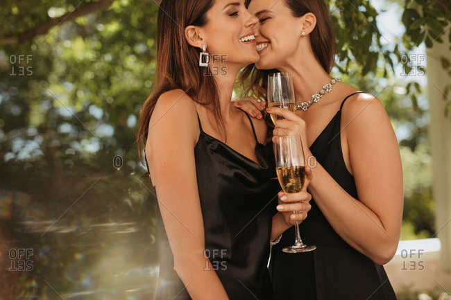 Two elegantly dressed women smiling with champagne glasses. Female friends enjoying at an outdoor party.
