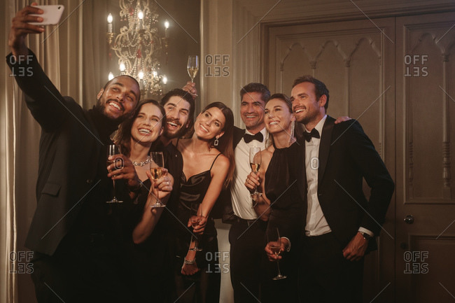 Man taking selfie with his friends at party. Group of men and women raising a toast and posing for a selfie at celebration event.
