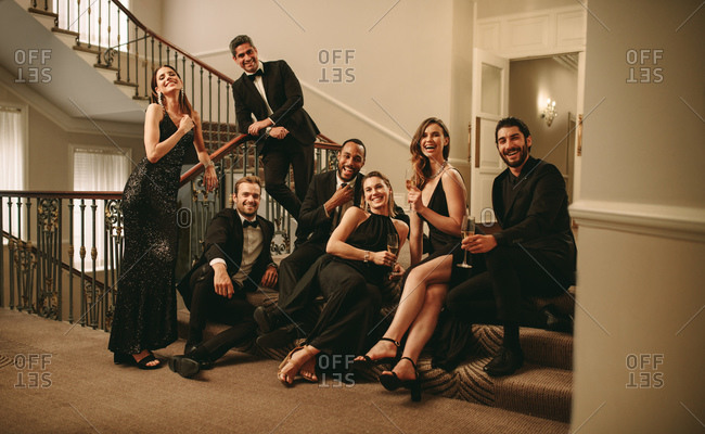 Multi-ethnic group of men and woman sitting at stairs and looking at camera. Large group of socialites enjoying at gala night.