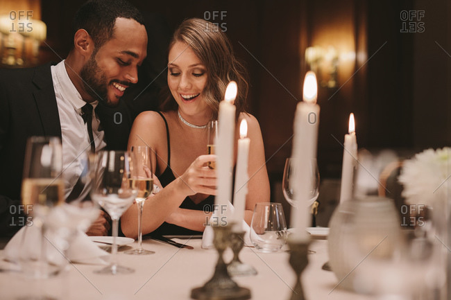 Loving couple sitting together at dinner party with glass of champagne. Man and woman enjoying at a gala dinner party.