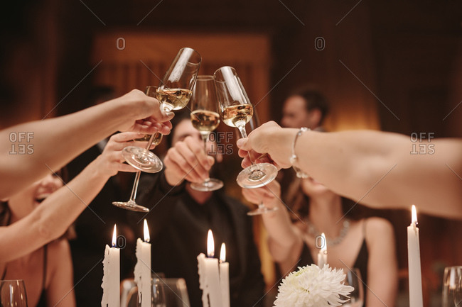 Group of men and women toasting champagne at a dinner party. Group of friends celebrating with drinks at gala night.