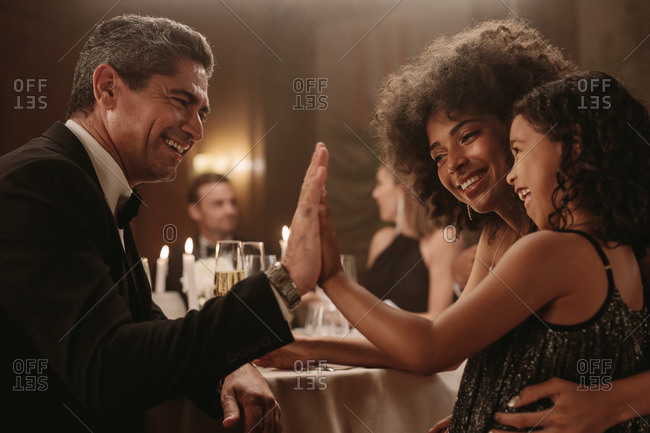 Mature man playing with a girl at dinner party with friends sitting around a dining table. Man giving high five to a little girl at gala night party.