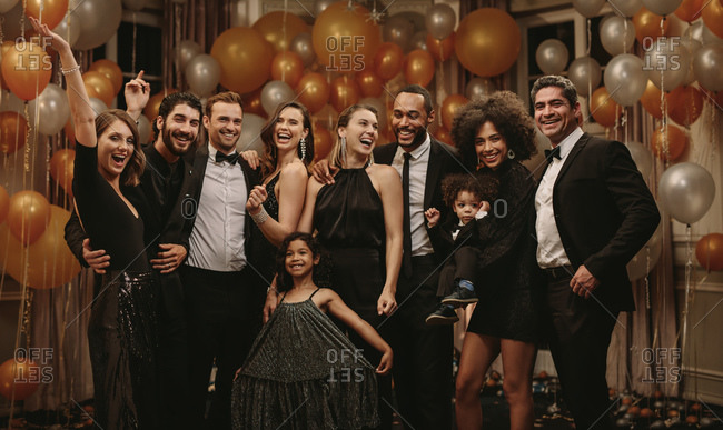 Group portrait of socialites on new years eve party. Diverse group of people with a cute girl standing together looking at camera and smiling.