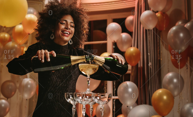 Beautiful woman pouring two bottles of champagne into glasses tower at gala night party. Smiling female in evening gown filling pyramid of glasses with champagne.