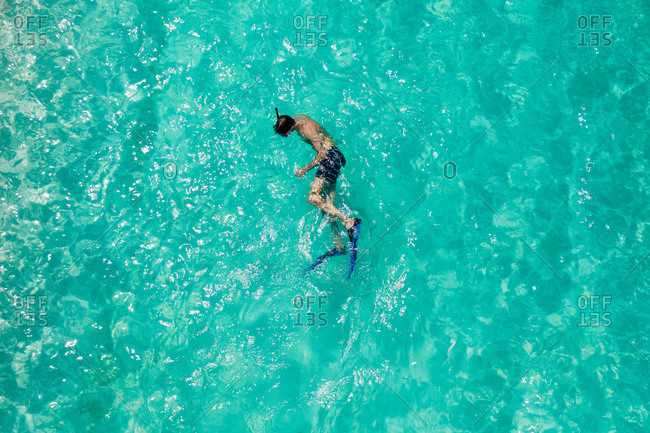 Aerial view of a man enjoying water activities in the sea. Man swimming in clear sea water wearing flippers and snorkel.