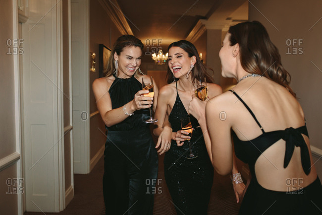 Group of women having a great time gala night. Female socialites enjoying with drinks at a gala night party.