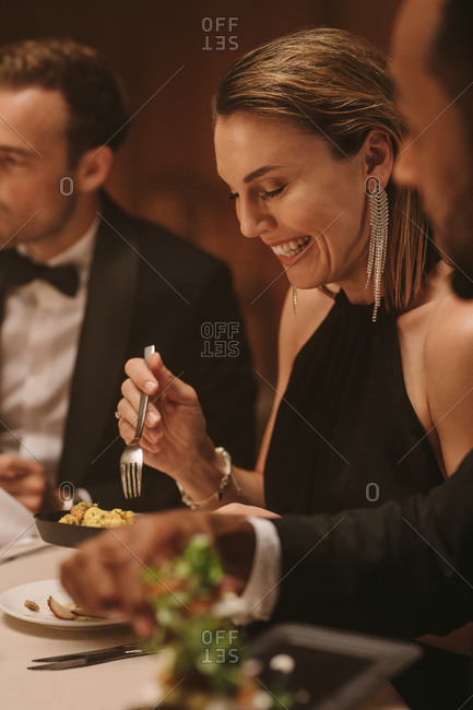Beautiful woman enjoying dinner with friends at party. Group of millennials enjoying dinner together.;