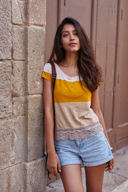 Serene woman casually leaning against a wall and looking at the camera