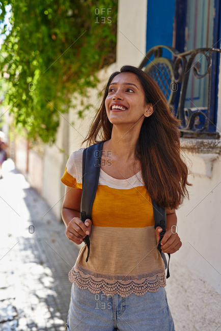 Elated woman standing along the side walk holding onto backpack and looking up