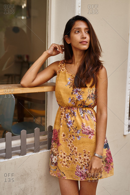 Pensive lady leaning against a window shelve on one arm while gazing to the side