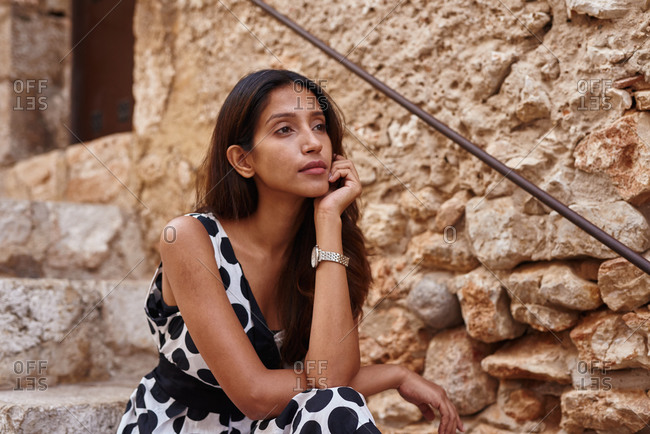 Pensive lady sitting on stairs in deep thought looking ahead