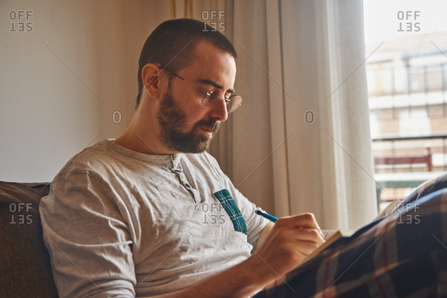 Busy middle-aged guy sitting and writing in a casual manner