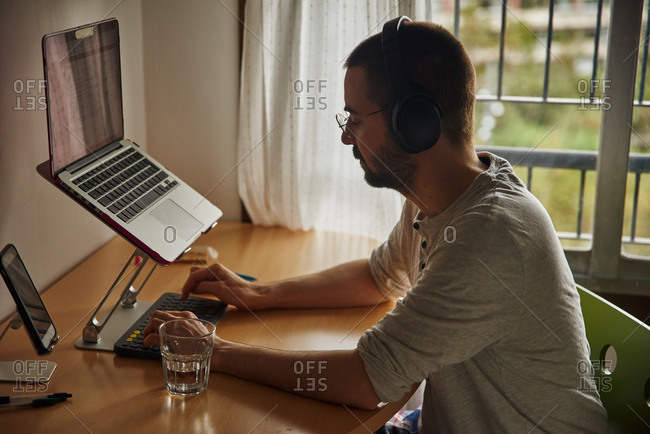 Preoccupied middle-age man looking at his keyboard in mid-typing using headphones