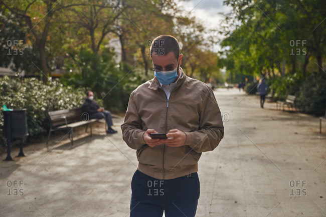 Intrigued man standing along a pathway texting using a blue mask and being surrounded by trees