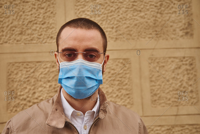 A calm middle-aged man wearing a blue mask while standing next to a textured wall