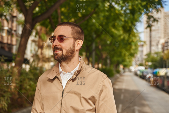 A blissful man standing on a side-walk smiling while looking away