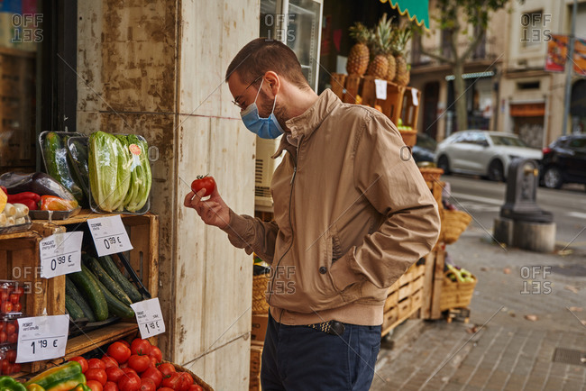 Intrigued man outside looking at a tomato with one hand in his jacket pocket