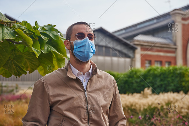 Expressionless man standing outside in a garden outside a huge building