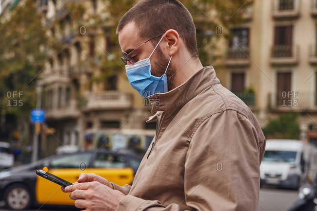 An actively engaged man texting while outside in the street and wearing a mask
