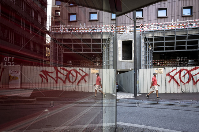 Porto, Portugal - August 29, 2020: Reflection of a man walking near a construction site