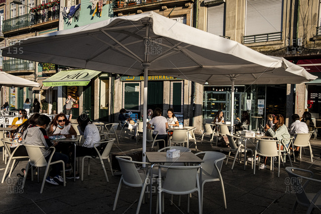 Porto, Portugal - August 29, 2020: People sitting outside on a coffee shop terrace