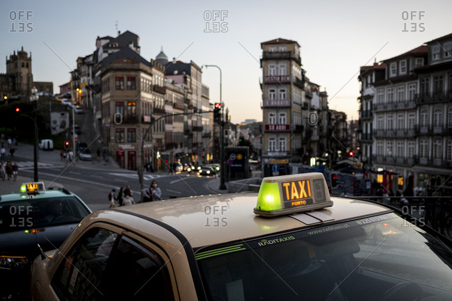 Porto, Portugal - August 29, 2020: Taxis on busy street downtown at dusk