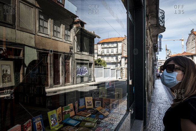 Porto, Portugal - August 31, 2020: Woman wearing a mask looking at a bookstore