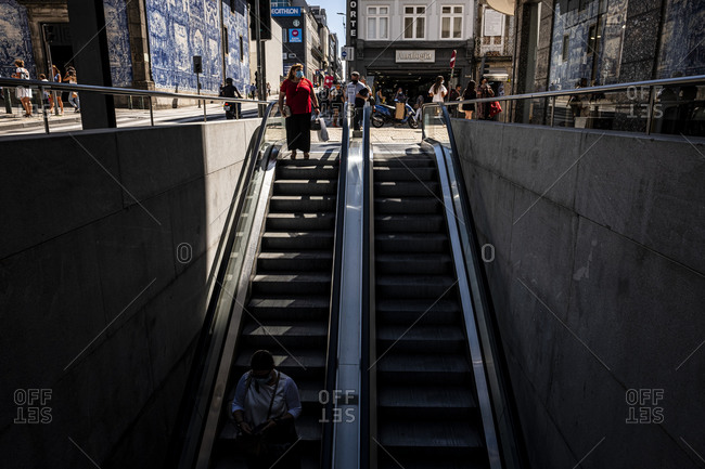 Porto, Portugal - August 31, 2020: People entering Bolhao Metro Station via escalator