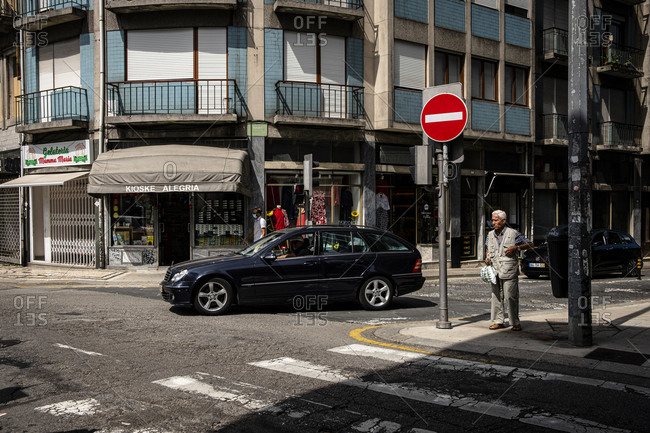 Porto, Portugal - August 31, 2020: Man waiting to cross the road in downtown Porto