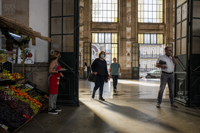 Porto, Portugal - August 31, 2020: People walking at Sao Bento station by a fresh fruit stand