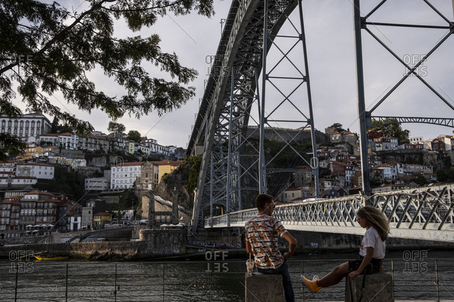 Porto, Portugal - August 31, 2020: Couple by the Douro river overseeing Porto's Ribeiro