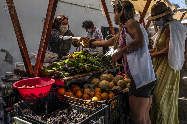 Caminha, Portugal - September 2, 2020: Women buying fresh vegetables in a street market
