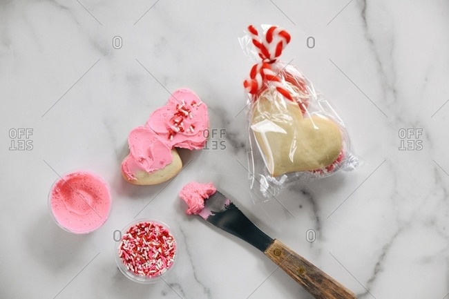 Heart cookies being iced from kit with frosting and sprinkles