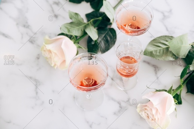 Blush wine served in three glasses by roses on marble surface