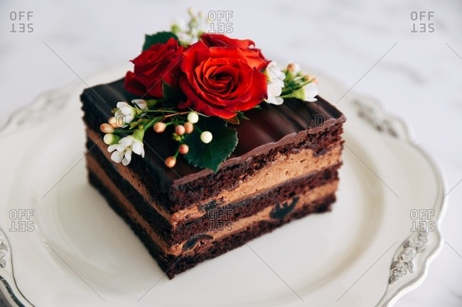 Layered chocolate cake topped with red roses
