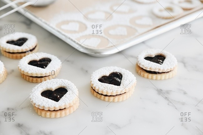 Heart Linzer cookies with powdered sugar beside baking tray