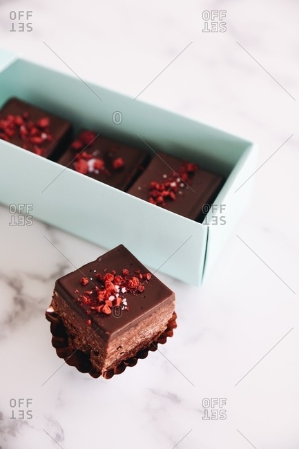 Fudge in and beside gift box on marble surface