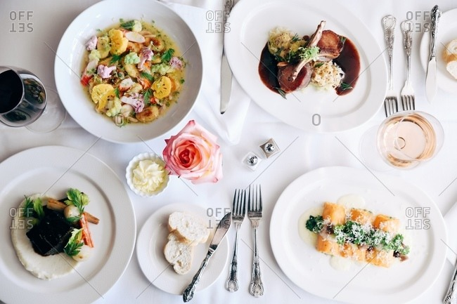 Overhead view of a variety of gourmet dishes served in restaurant with wine