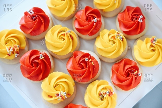 Sugar cookies topped with red and yellow frosting with sprinkles