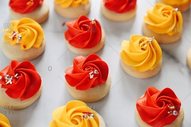 Close up of sugar cookies topped with red and yellow frosting with sprinkles on marble surface
