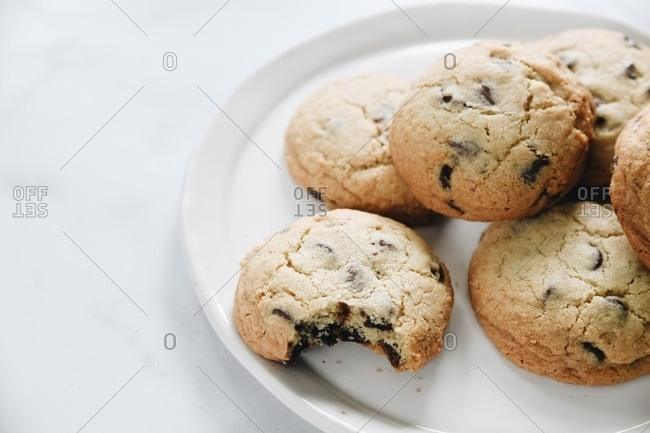 Chocolate chip cookies on plate on marble surface, one with bite taken out of it