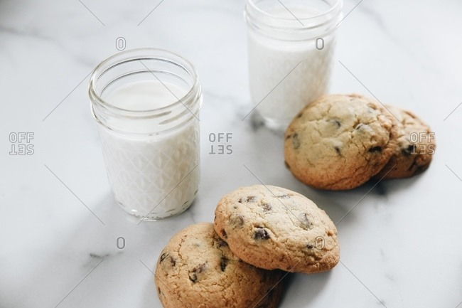 Chocolate chip cookies on plate on marble surface with glasses of milk