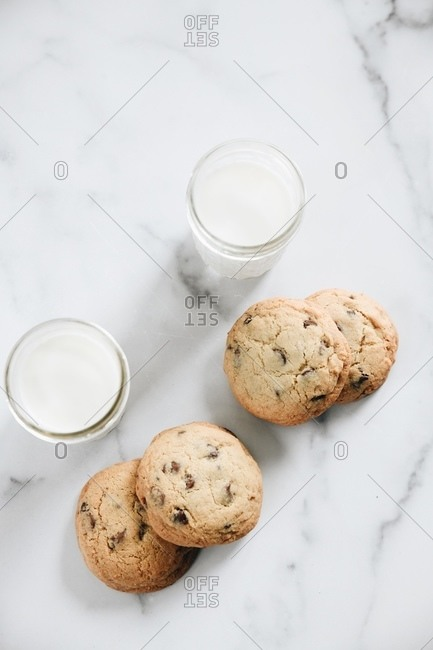 Overhead view of chocolate chip cookies on plate on marble surface with glasses of milk