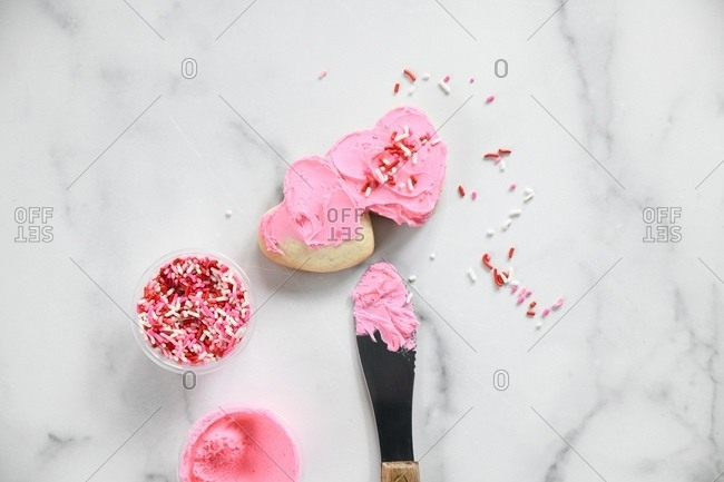 Heart Valentine's cookies being iced with pink frosting and sprinkles